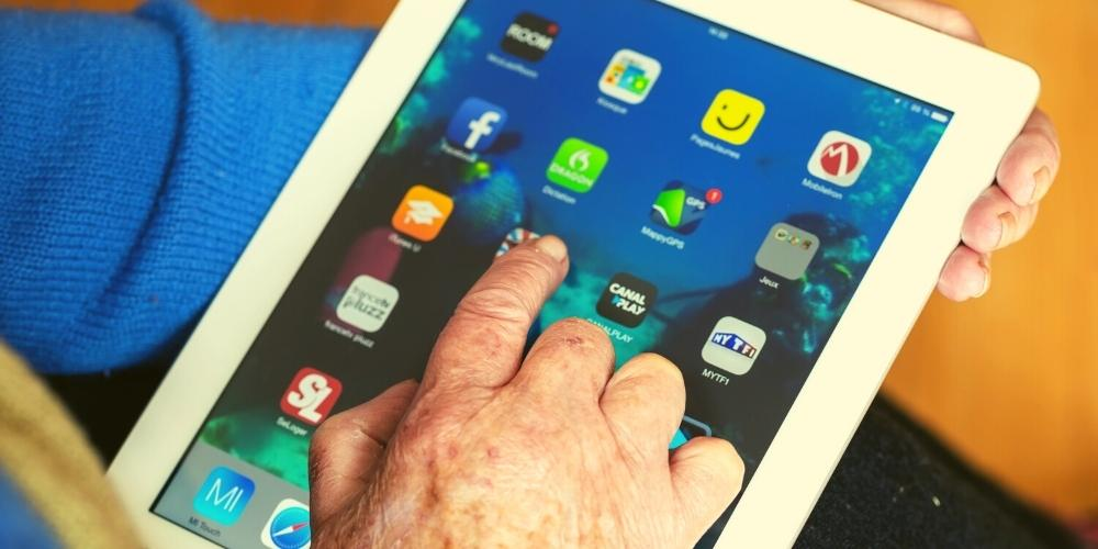 Senior citizen opening a fun brain games app on an iPad.