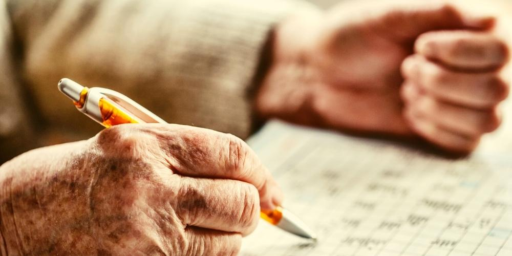 Photo of a senior lady doing a Sudoku brain game puzzle.