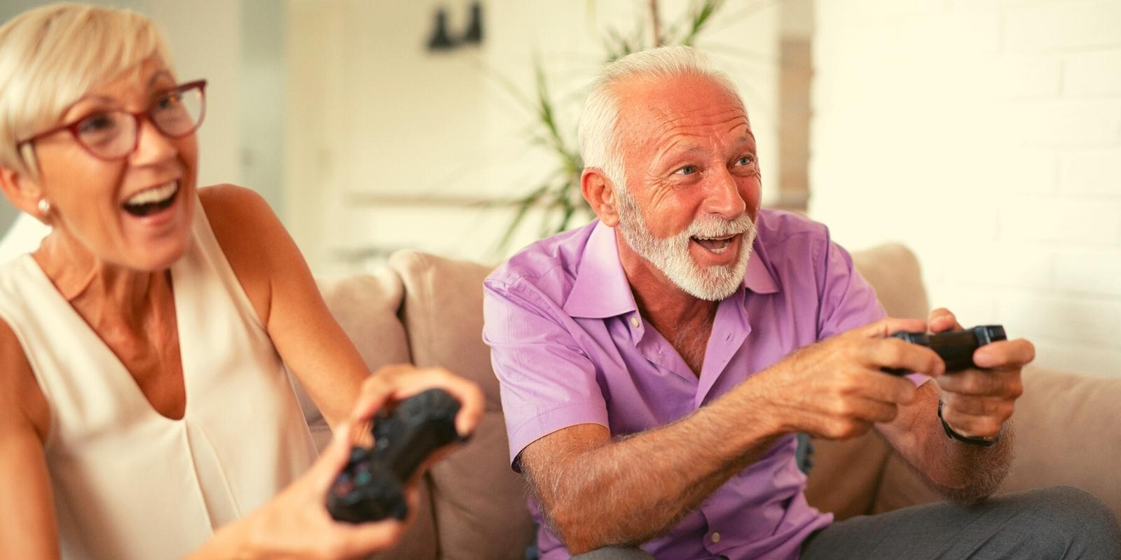 Elderly couple enjoying playing computer games for senior citizens together.