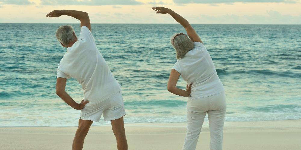 Seniors enjoying yoga on the beach